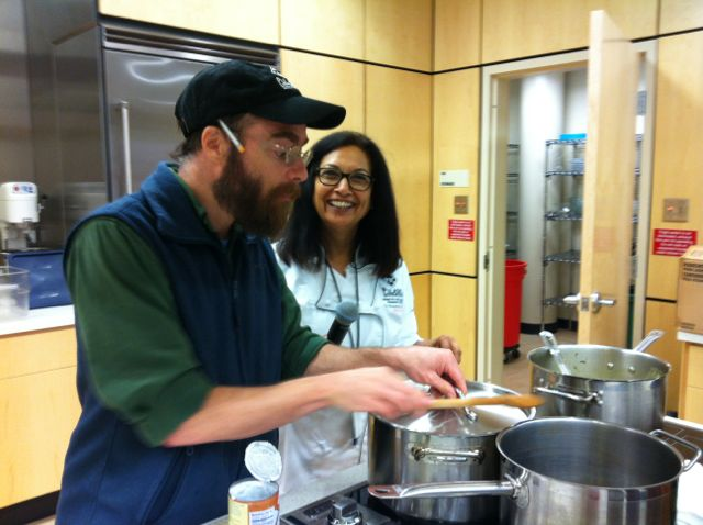 Root Café owner and chef Jack Sundell prepares the restaurant's Coconut Curry Collard Greens with Dr. Meenakshi Budrahaja.